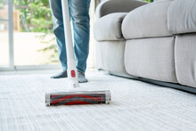 Asian Women Using Wireless Vacuum Cleaner Cleaning Carpet In Living Room At Home. Closeup