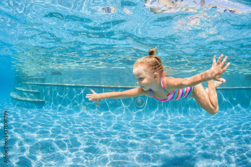 Fotomural Funny portrait of child learning swimming, dive in blue pool with fun - jumping deep down underwater with splashes