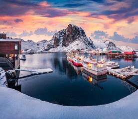 Sunrise on Hamnoy port with Festhaeltinden mount on background, Norway, Europe. Frosty morning scene of Lofoten Islands. Snowy winter seascape of Norwegian sea. Calm outdoor scene over polar circle.