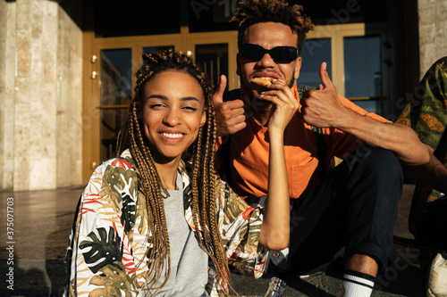 Fototapeta Optimistic african friends loving couple sitting outdoors and eating pizza