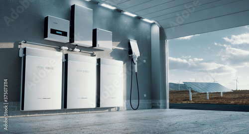 Concept of a home energy storage system based on a lithium ion battery pack situated in a modern garage with  view on a vast landscape with solar power plant and wind turbine farm Canvas