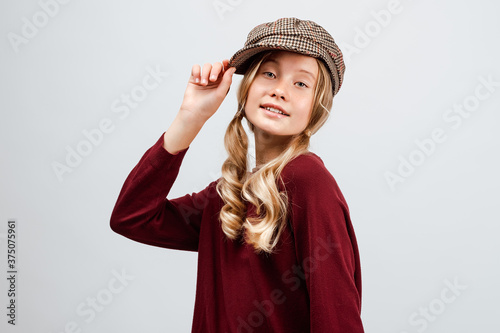 Beautiful blonde girl 10-12 years old wearing in cap and casual sweater, posing in the Studio Wallpaper Mural