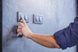 canvas print picture - Close up of finger turn off on light switch at the wall. Energy saving concept