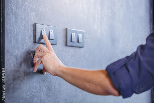 Fotografie, Obraz Close up of finger turn off on light switch at the wall