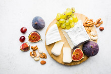 Camembert Or Brie Cheese With Fresh Figs, Honeycomb And Glass Of Wine On Serving Board Over White Backdrop, Top View, Copy Space