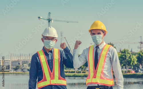 Engineers saluting each other by touching elbows,Two business people shake hand Fototapet