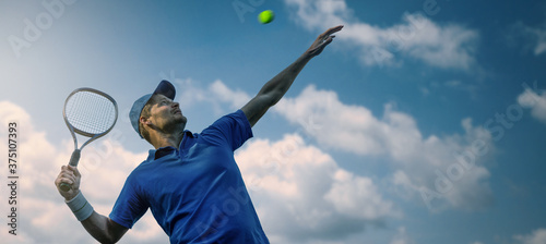 Fotografie, Tablou male tennis player hitting ball with racket against blue sky