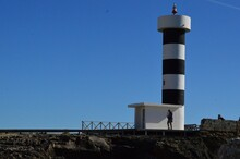 Black And White Lighthouse Tower And Blue Sky Background