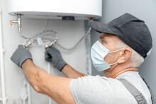 Plumber Man In Medical Mask Installing Boiler Water Heater In Bathroom
