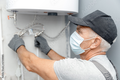 Canvas Plumber man in medical mask installing boiler water heater in bathroom