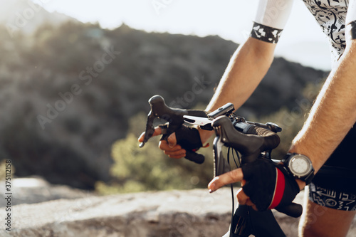 Foto Hands of a professional cyclist in gloves on handle bar of a bicycle