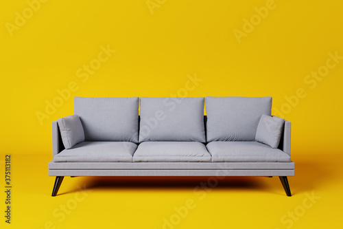 Grey couch with pillows on studio yellow background. Tableau sur Toile