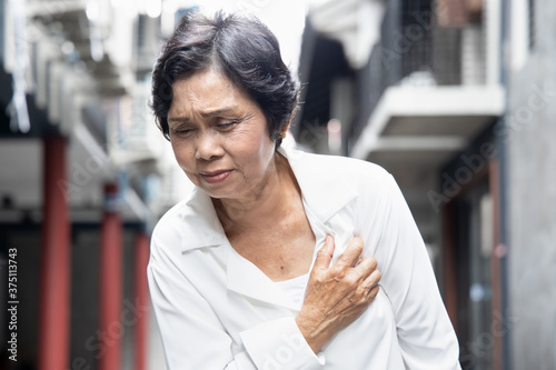 Fototapeta sick old senior woman suffering from hearth attack or cardiac arrest