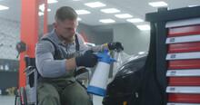 Mechanic On Wheelchair Applyin...