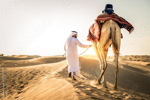 Arabian man with camel in the desert Fototapete