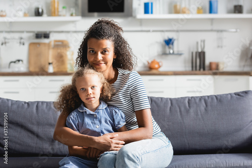 young african american woman embracing daughter and looking at camera while sitt Fototapeta