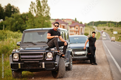Two asian brothers man wear on all black posed near suv cars. Canvas Print