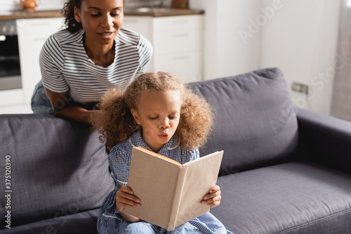 Slika na platnu african american nanny in striped t-shirt looking at concentrated girl sitting o
