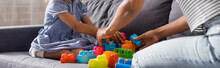 Cropped View Of African American Babysitter And Child Playing With Colorful Building Blocks On Sofa, Horizontal Image