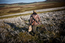 A Hunter With His Trophy After A Big Hunt In Scotland. Walking In The Highlands With A Dead Deer's Head In His Hand And A Shotgun On His Back.
