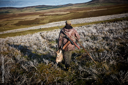 Fotografiet A hunter with his trophy after a big hunt in Scotland