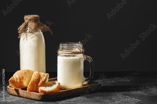 Fototapeta Glass of milk with sliced baguette on wooden board