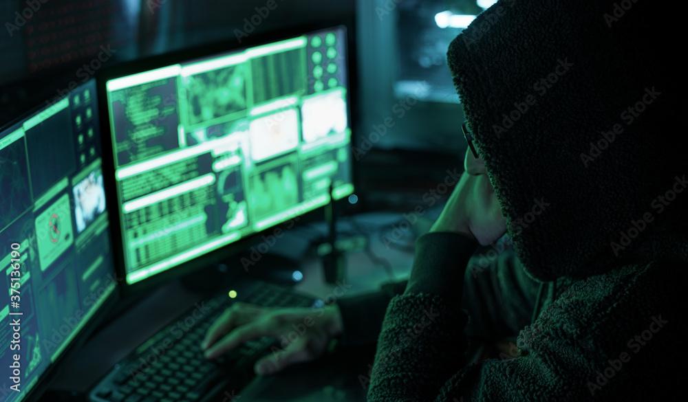 Fototapeta Dangerous hooded hacker in his hideout place which has a dark atmosphere, multiple displays