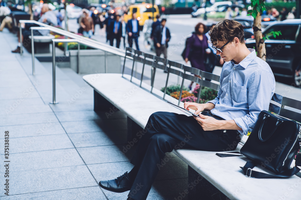 Fototapeta Young man using tablet on bench