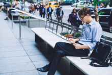 Young Man Using Tablet On Bench