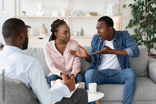Photo Anxious black man complaining about relationship problems with wife at counsello