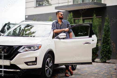 Successful arab man wear in striped shirt and sunglasses pose near his white suv car Poster Mural XXL