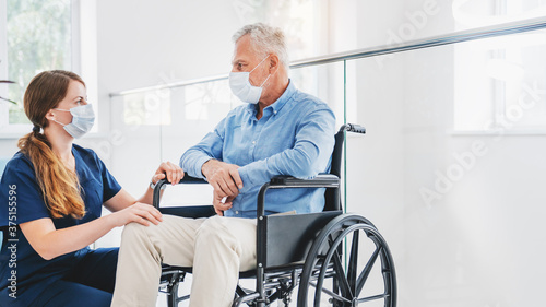 Caucasian nurse taking care of senior male patient on wheelchair in hospital Fototapeta