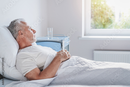 Fotografija Side view of thoughtful senior male patient in hospital bed in ward room