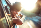 Fototapeta Londyn - Beautiful curly hair woman enjoying the breeze, looking out of the window's car while having a road trip