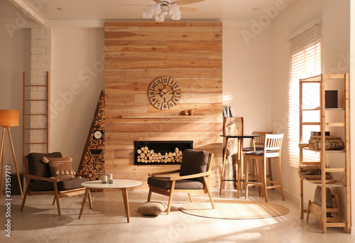 Decorative fireplace with stacked wood in cozy living room interior Fototapeta