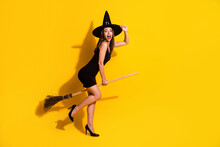 Full Length Body Size Profile Side View Of Her She Attractive Ecstatic Cheerful Cheery Lady Wizard Riding Broom Having Fun Event Magic Isolated Bright Vivid Shine Vibrant Yellow Color Background