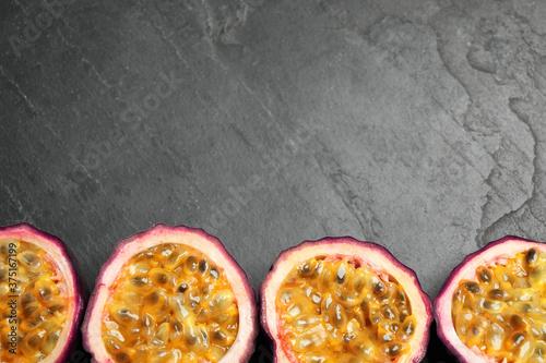 Obraz na plátně Halves of passion fruits (maracuyas) on black slate table, flat lay