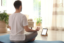 Man Practicing Yoga While Watc...