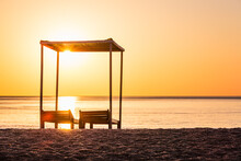Wooden Lounge Chairs And Canopy On The Beach