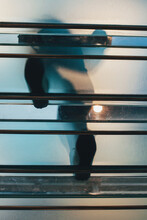 A Person's Feet Captured From Below Glass Stairs While Going Up The Stairs