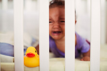 Baby Crying Behind The Bars Of Her Crib With Toy Rubber Duck