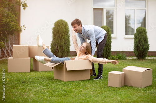 Fotografija Happy young lady having fun with her boyfriend, riding carton box outdoors on mo