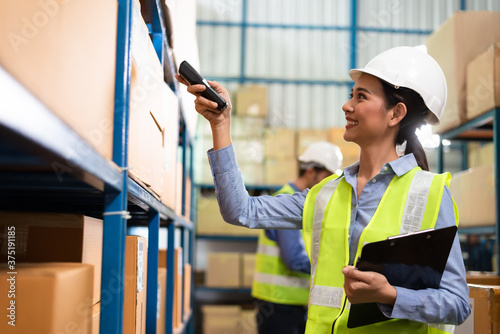 Fotomural Warehouse woman staff use bar code scanner checking stock and supply on site