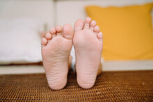 Close Up - Little Child Barefooted Feet On A Bed.