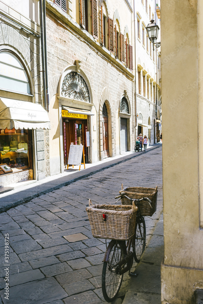 Florence, Italy. Bicycle with straw baskets leaning on the wall of an alley in Florence