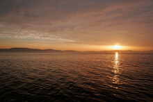 Sunset Between The Cloudsheet And The Sea With Twinkling Golden