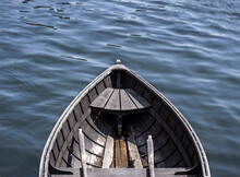 Empty Wooden Rowboat Floating In Calm Waters
