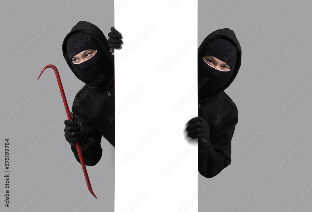 Fototapeta Burglar concept,Masked thief in balaclava with crowbar on gray background