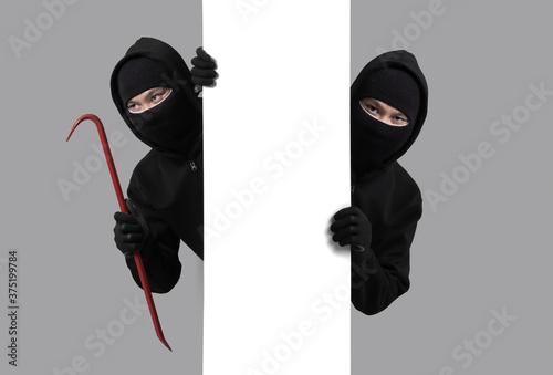 Fototapeta Burglar concept,Masked thief in balaclava with crowbar on gray background