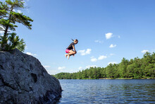 Girl Does A Cannonball Jump Off A Rock Into The Lake